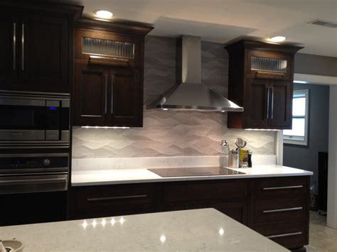 remodeled kitchen wavy porcelanosa backsplash ge monogram induction cooktop cambria countertop