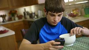 With His Smart Phone A Teenage Boy Listens To Music And ...