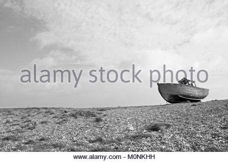 Old Boat Washed Up by Old Wooden Fishing Boat Washed Up On A Shingle Beach Stock