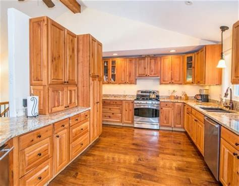 the kitchen features natural cherry cabinets granite