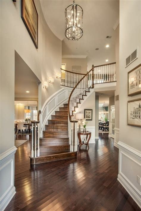 traditional entryway  wainscoting high ceiling chandelier dark hardwood floors wall