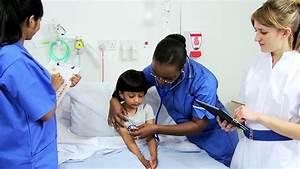 Multi-ethnic nursing staff recording pediatric patient's ...