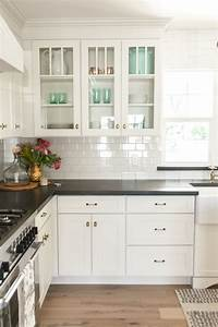White kitchen cabinets black countertops and white subway for Kitchen cabinet trends 2018 combined with large glass wall art