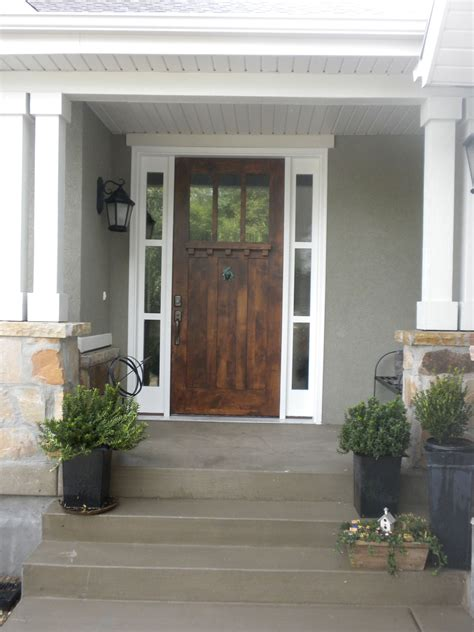 front door like how its a grey house and white trim and real wood door looks great with the