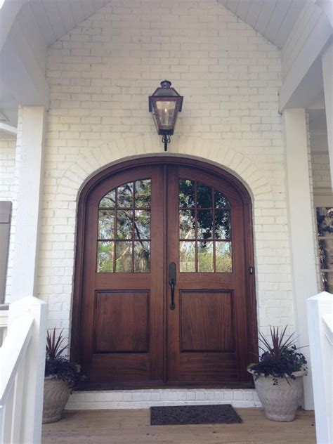 Wood Front Door With Door by Brown Arched Glass Front Door On White Brick Home Build