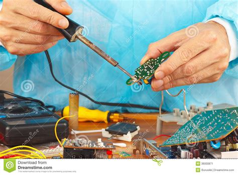 Serviceman Soldering Circuit Board With Iron