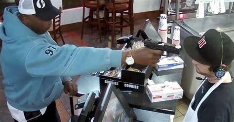 robber points gun   head  shop worker