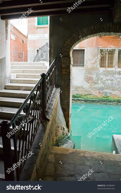 Old Bridge And Green Water Of A Canal Venice Italy Stock