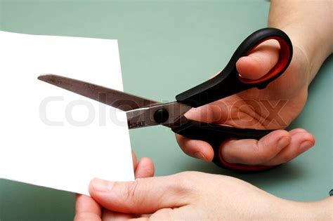 women hand  cutting paper  scissors stock photo