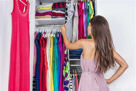 Woman Choosing Clothes To Wear In Clothing Closet Stock