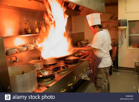 cuisine oriantale chef cooking with flaming wok in a restaurant
