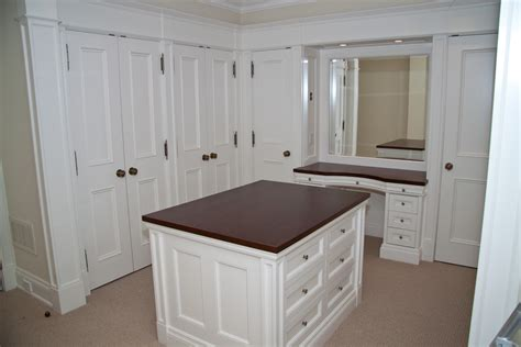 walk in closet with make up counter and dresser island