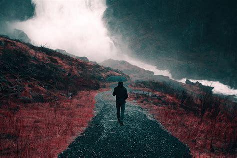 silhouette of man walking waterfalls holding umbrella ...