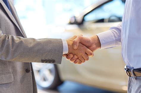 handshake in auto dealership - Selling My Car 4 Cash