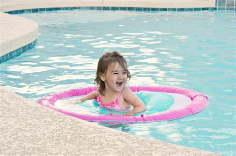 Toddler In Backyard Pool With Swimways Baby Spring Float