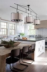 A three light drum pendant hangs over white kitchen