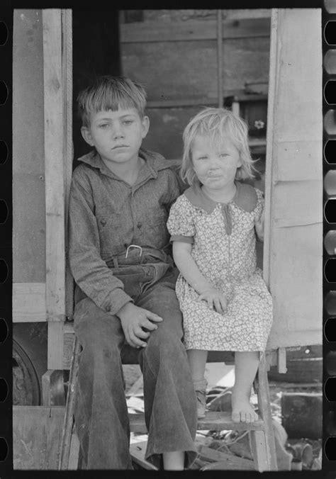 children  migrants sitting  doorway  trailer
