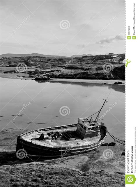 Find A Fishing Boat In Ireland by Old Beached Fishing Boat On Irish Beach In Black And White