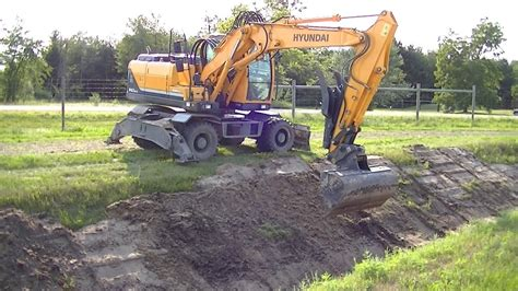 hyundai    wheeled excavator cleaning  ditch youtube