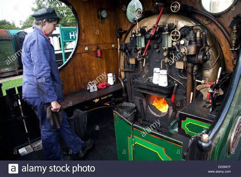 A Female Engine Driver Working The Footplate Of A Steam