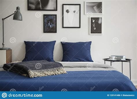 This modern coffee table brings a splash of glamour to any living room or office space. Close-up Of Bed With Blue Bedding And Dark Colored Blanket. Bedside Table With Books And Coffee ...