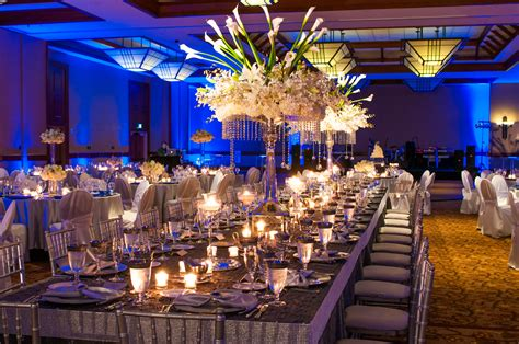 banquet table decorations white flowers on the high glass vase plus candles and eating utensils placed on the long table