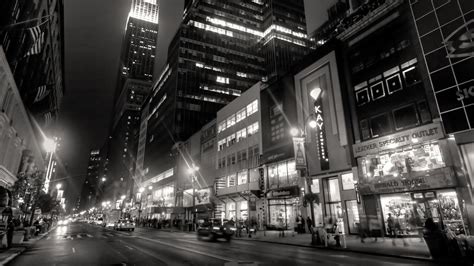 black and white picture of road between lighting buildings