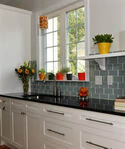 black counter top with aqua green backsplash tiles and
