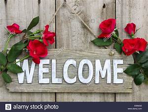 Weathered wood welcome sign hanging on wooden door with