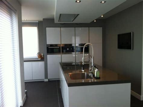 hoogglans witte greeploze keuken met kook spoeleiland en strakke kastenwand met verticale