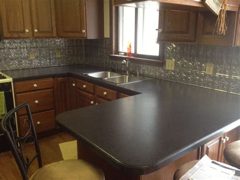 Black Corian by Black Corian Vs Granite Countertop With Tile Backsplash