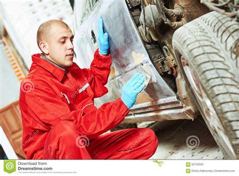 Worker Applying Car Body Repair Putty Stock Photo