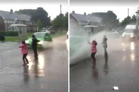 rain soaked children getting splashed cars drenched risk road birmingham puddle mum parents vehicles