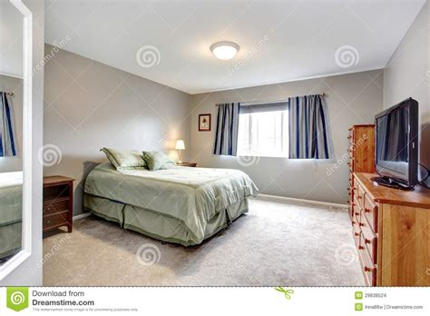 large grey bedroom with dresser tv and blue curtains