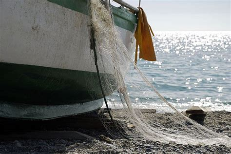 Fishing Boat Net by Fisherman With Net And Boat