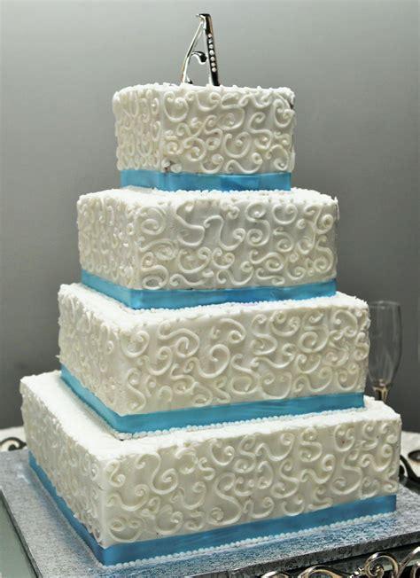 tier square wedding cake  swirl design blue ribbon