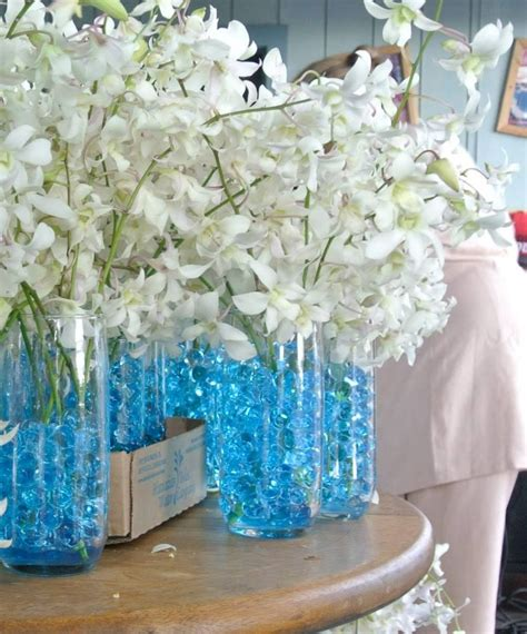white orchids centerpiece blue water beads glass cups