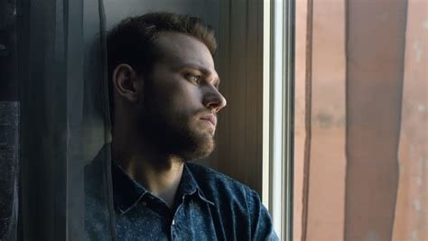 Young Sad And Depressed Man Looking Out Window Stock
