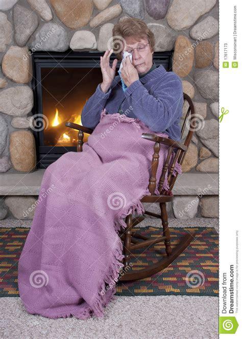 senior sad cry rocking chair fireplace stock photos