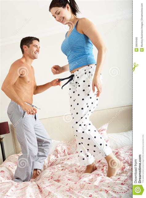 couple bouncing  bed  stock photo image