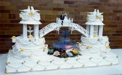 Unique Double Wedding Cake connected by bridge with bride & groom & fountain in the middle