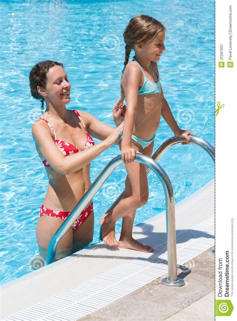 mother helping daughter    pool stock image