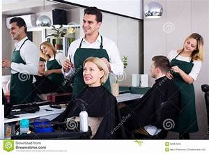 Professional stylist cutting hair of elderly blonde