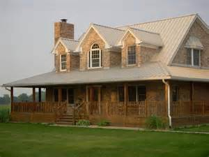 country home with wrap around porch large circle driveway with flagpole in middle house sits