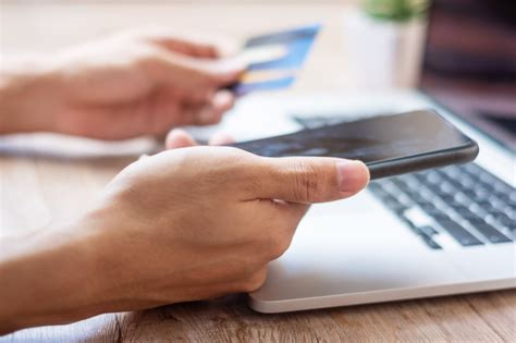 Are smartphone payment methods as secure as credit cards? Hands holding credit card and smartphone | Premium Photo
