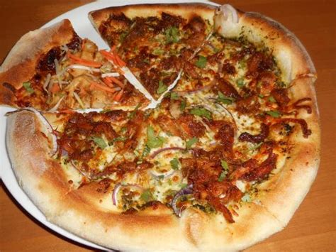 thai chicken pizza with a slice of carnitas pizza