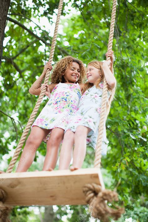 smiling girls standing  tree swing stock image