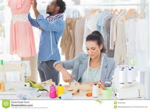 fashion designer fashion designer cutting textile at desk royalty free stock photo image 31554445