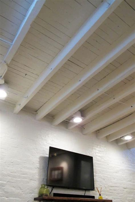 exposed floor joists  basement painted white