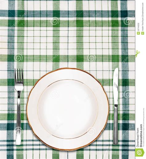 white plate  green checkered tablecloth stock photo